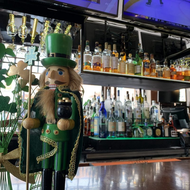 St. Patrick's Day nutcracker on a bar with liquor in the background