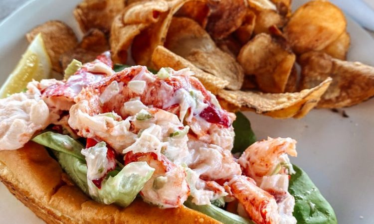 A classic mayo lobster roll on a plate with chips.